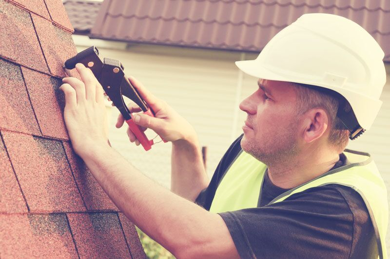 man installing roof shingles, how home renovations can reduce your insurance rates