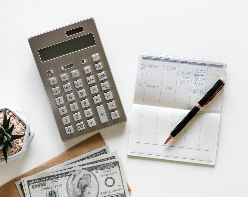 cash, calculator, and checkbook; home insurance claim payment