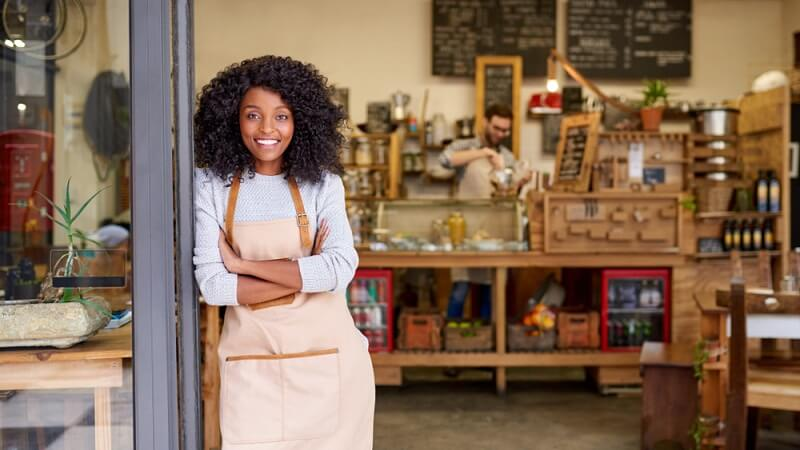 small business owner standing in front of store, why you need business insurance