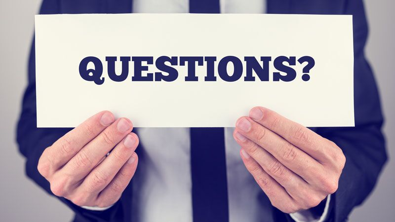 "man holding a sign that says ""questions?"", update your business insurance to fit your company's evolving needs"