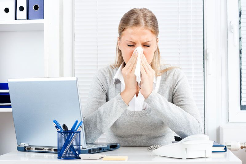 employee at desk with the flu, stop the spread of germs by cleaning your devices this cold and flu season