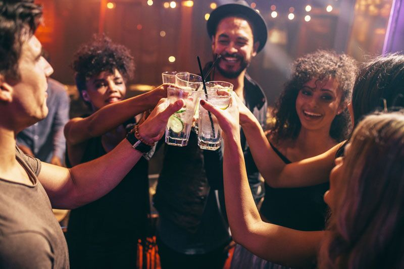 group of friends doing cheers, make your holiday party less stressful
