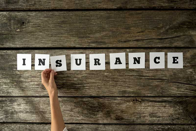 """person spelling out """"insurance"""" with paper letters, different types of home insurance"""